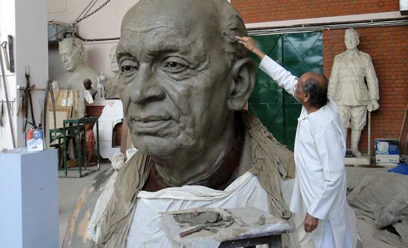 Finishing touches on head of 30-foot statue in the artist's workshop.